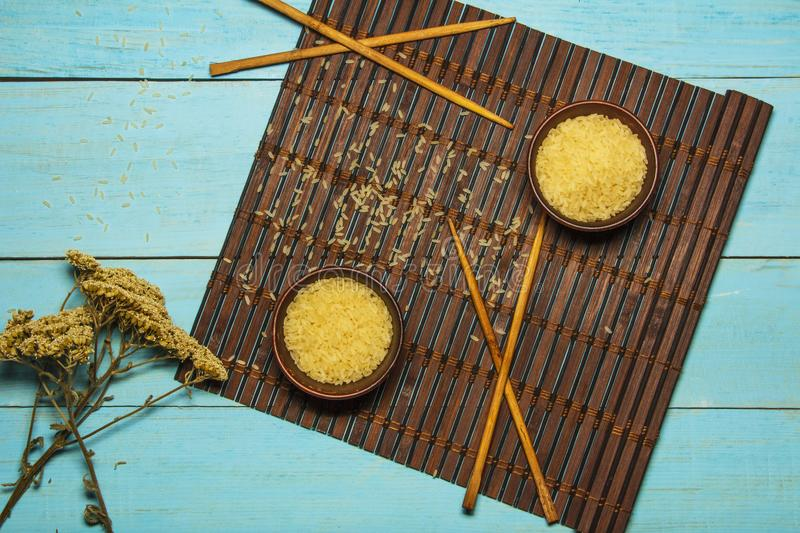 Japanese rice in a wooden bowl. Wooden chopsticks On the table of a bamboo mat. Asian cuisine. View from above. stock photos