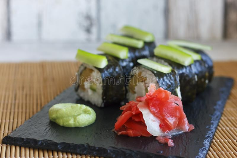 Japanese rolls with cucumber, crabs and omelet on a black board with wasabi and ginger royalty free stock images
