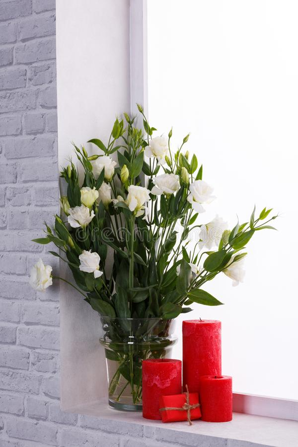 Japanese Roses In A Vase Next To Candles And A Small Gift On The