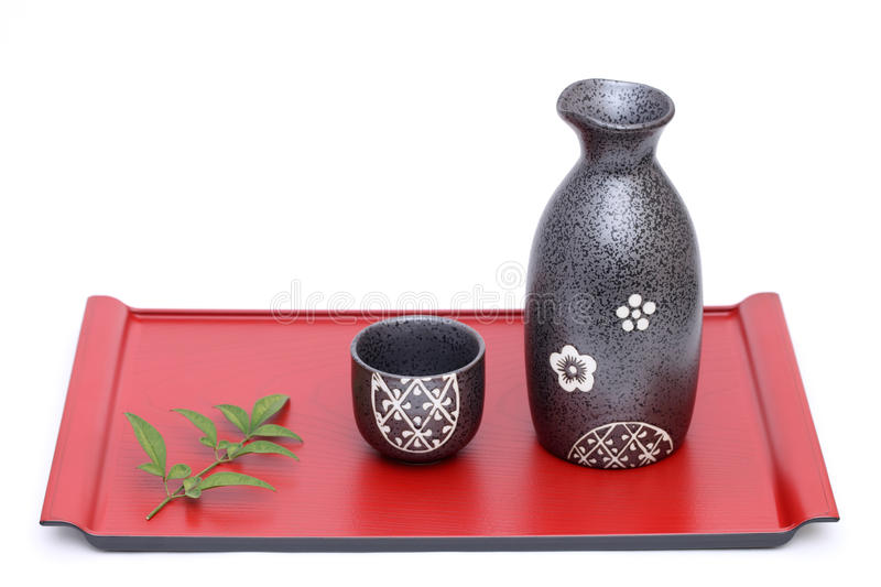 Japanese sake bottle and cup. On tray, isolated on white background stock image