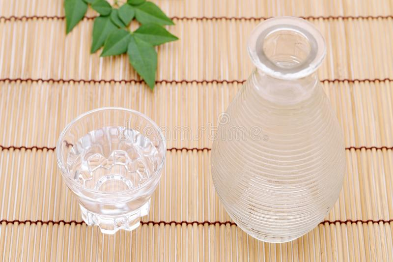 Japanese sake in glass cup and jar. Japanese sake in transparent glass cup and jar on bamboo table royalty free stock photo