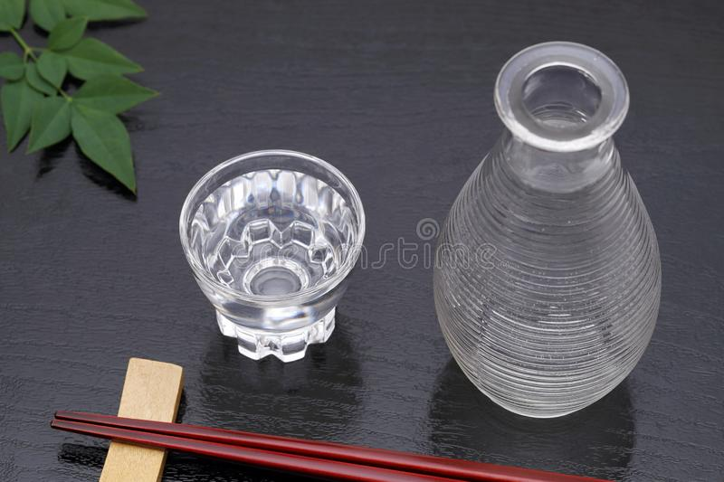 Japanese sake in glass cup and jar. Japanese sake in transparent glass cup and jar on black background stock photos