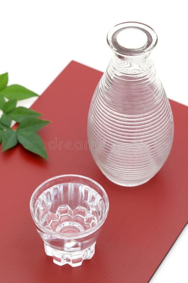 Japanese sake in glass cup and jar. Japanese sake in transparent glass cup and jar on white background stock image