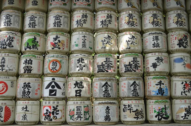 Japanese sake rice wine barrels. With decorative writing in a japanese temple in Tokyo royalty free stock images