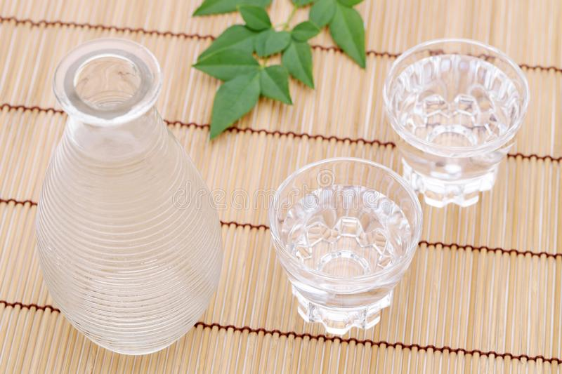 Japanese sake in glass cup and jar. Japanese sake in transparent glass cup and jar on bamboo table stock images