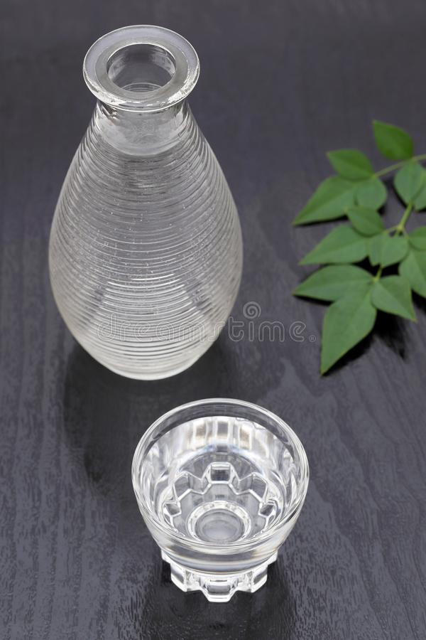 Japanese sake in glass cup and jar. Japanese sake in transparent glass cup and jar on black background stock photography