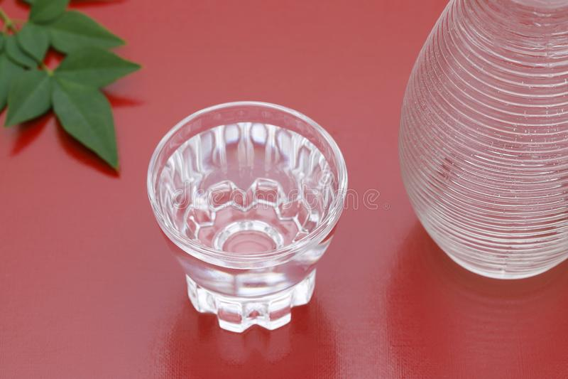 Japanese sake in glass cup and jar. Japanese sake in transparent glass cup and jar on red background royalty free stock images