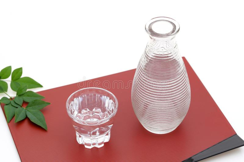 Japanese sake in glass cup and jar. Japanese sake in transparent glass cup and jar on white background royalty free stock image