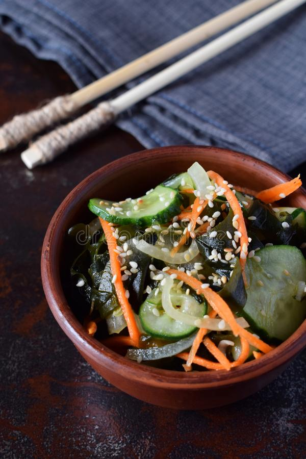Japanese salad sunomono with wakame, cucumber, onion and carrot sprinkled sesame and chopsticks. Asian raw food.  royalty free stock image
