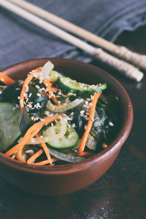 Japanese salad sunomono with wakame, cucumber, onion and carrot sprinkled sesame and chopsticks. Asian raw food.  stock images
