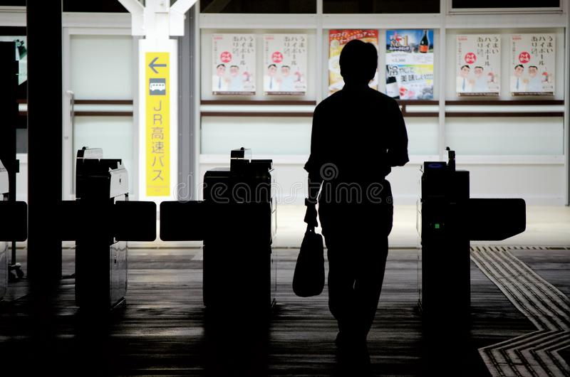 Japanese salaryman going through the exit of the Shinjuku station, Japan. Shinjuku is the busiest one is the world. The world is b. Ig enough to explore more and stock photo