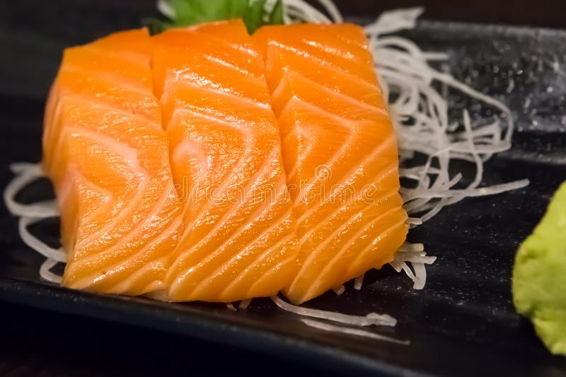 Japanese Salmon Sashimi on a Plate. Japanese raw salmon sashimi on a plate.  Sashimi is a Japanese delicacy consisting of fresh raw fish into thin pieces and royalty free stock photography