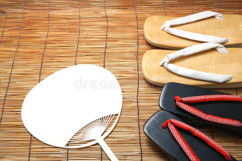 Japanese sandals for men and women and fan on bamboo blinds. Concept of Japanese summer stock images