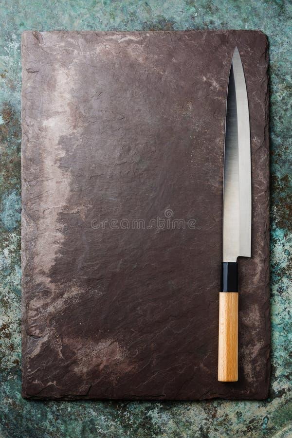 Japanese sashimi knife on black slate background. Japanese sashimi knife on black stone slate background texture royalty free stock photos