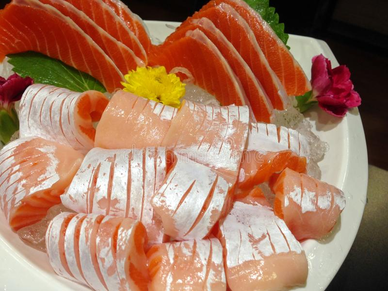 Japanese sashimi salmon buffet in white disk with ice. stock photography