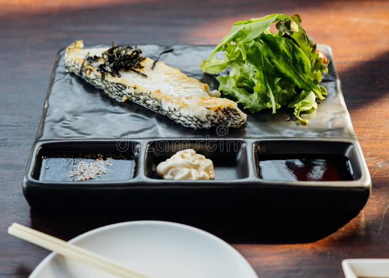 Japanese Sea Bass Fillet Steak served with salad, mayonnaise and Shoyu sauce on stone plate stock images