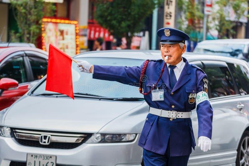 Japanese security guard. KOBE, JAPAN - NOVEMBER 17: Security Guard in Kobe, Japan on November 17, 2013. Unidentified security guard raises a red flag at a royalty free stock image