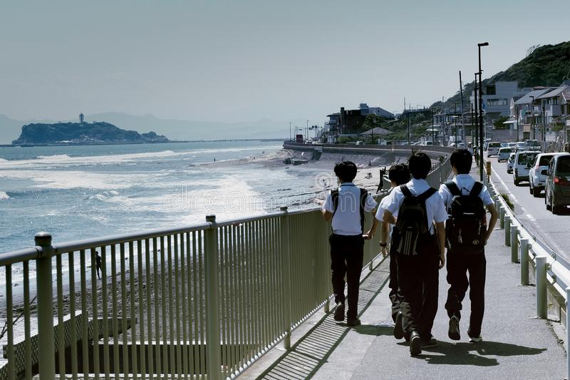 Japanese students are walking home on the beach stock image