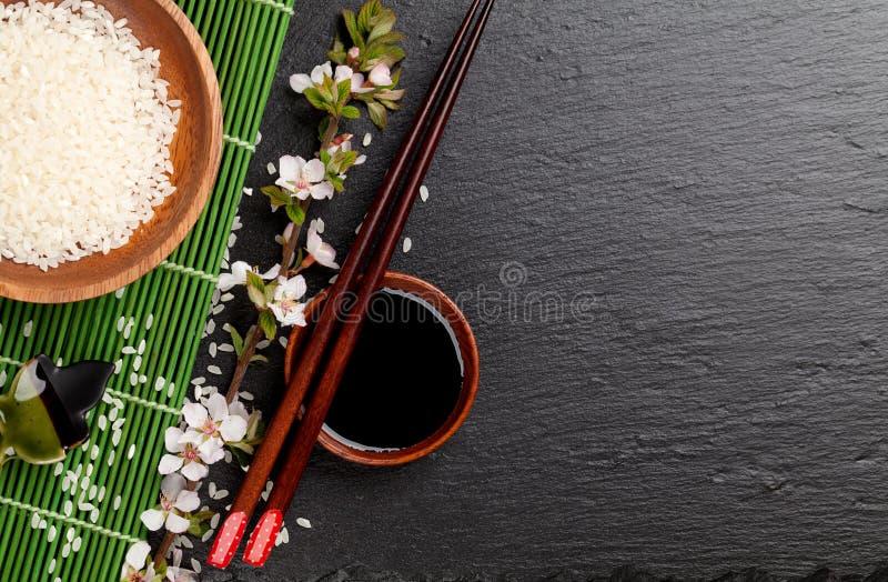 Japanese sushi chopsticks over soy sauce bowl, rice and sakura b stock photos