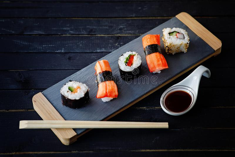 Japanese sushi dish. Sashimi Nigiri sushi with rice and salmon. And rolls with tuna and soya sauce on a dark wooden background. Japanese food style. Top view royalty free stock photos
