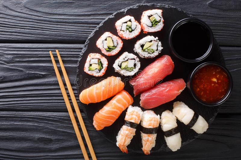 Japanese sushi food. Maki ands rolls with tuna, salmon, shrimp, crab and avocado with two sauces close-up on a slate. horizontal stock photos