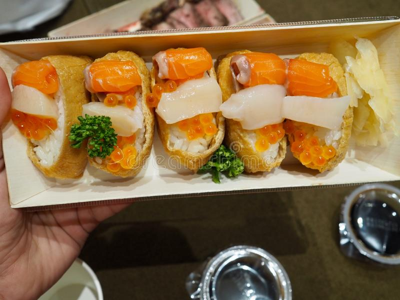 Japanese rice sushi wrap with tofu sheet topping with Hotate shell fresh salmon and egg & x28; Inari sushi& x29; royalty free stock images