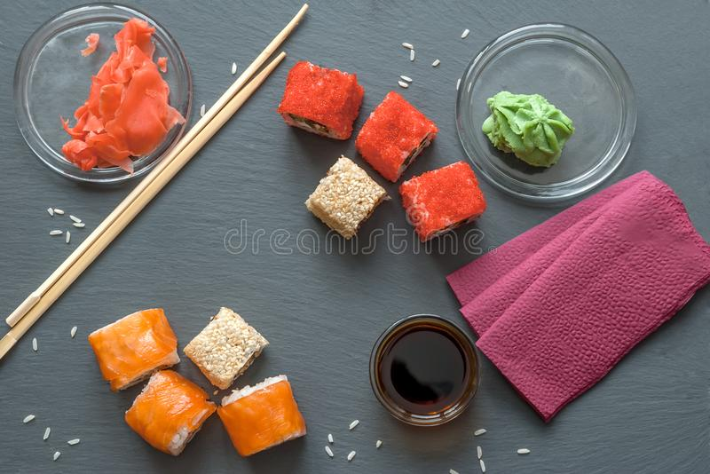 Japanese sushi made of rice and sea bass, shrimp and smoked eel with caviar of flying fish with Philadelphia cheese, chopsticks on royalty free stock image