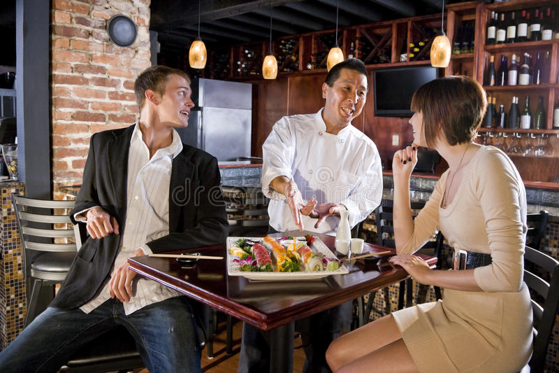 Japanese sushi restaurant, chef serving customers. Couple having sushi in Japanese restaurant talking with chef stock images