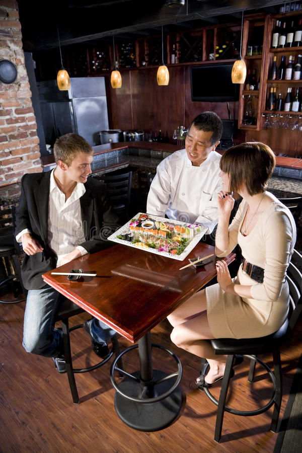 Japanese sushi restaurant, chef serving customers. Japanese sushi chef serving platter of sushi to young couple stock image