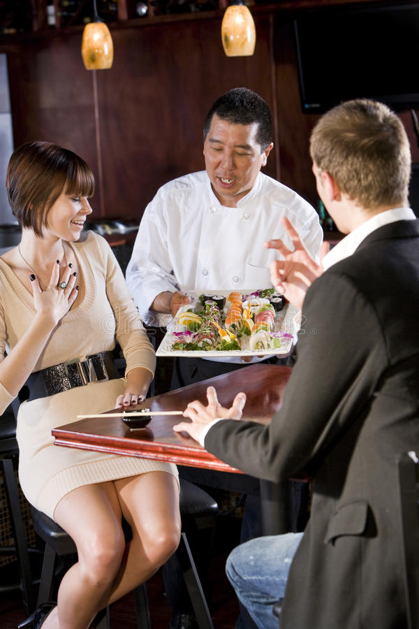 Japanese sushi restaurant, chef serving customers stock photography