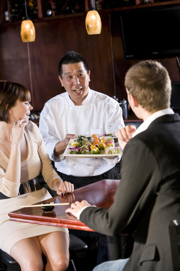 Japanese sushi restaurant, chef serving customers. Japanese sushi chef serving platter of sushi to young couple royalty free stock images