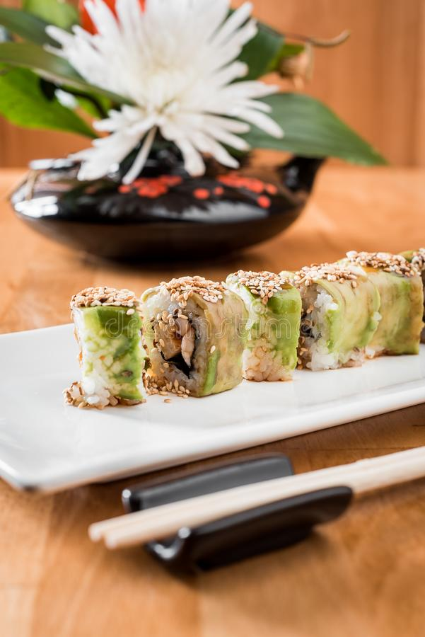 Japanese sushi roll green dragon with eel and avocado with ginger on a white plate. isolated. close up stock image