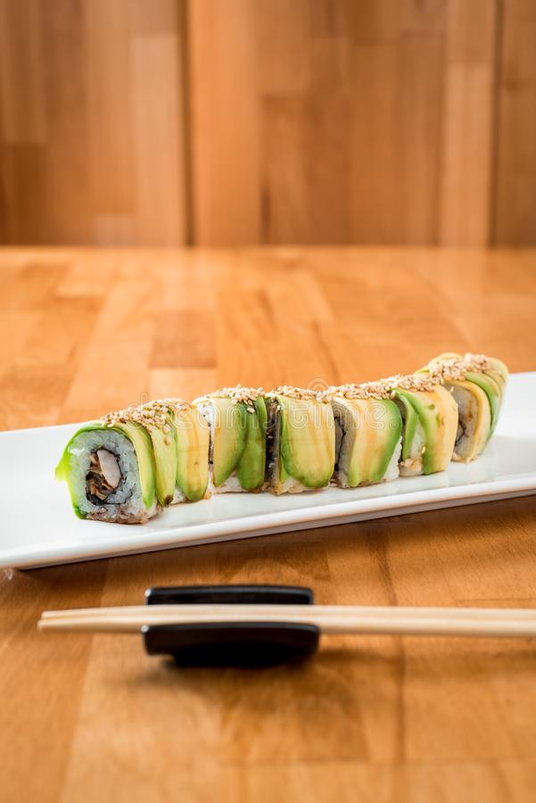 Japanese sushi roll green dragon with eel and avocado with ginger, lime, on a white plate stock image