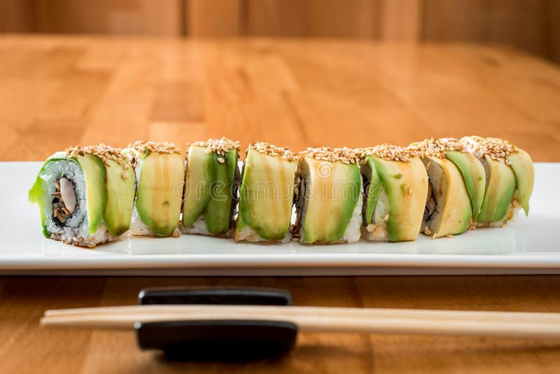 Japanese sushi roll green dragon with eel and avocado with ginger, lime, on a white plate royalty free stock images