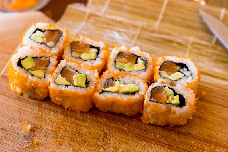 Japanese sushi and rolls with salmon, avocado, cucumber and flying fish caviar royalty free stock images