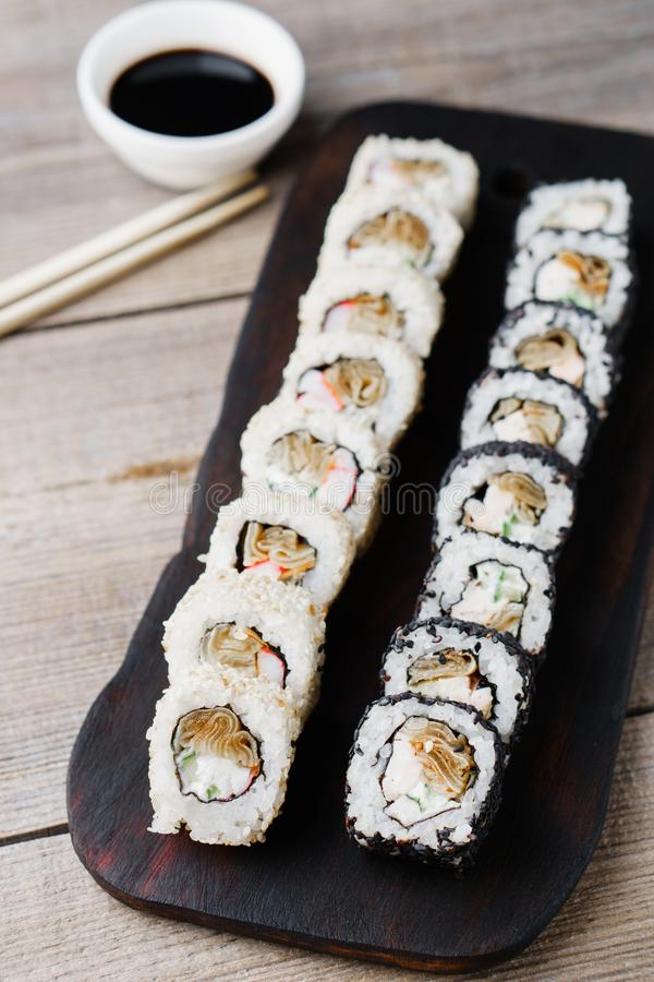 Japanese sushi rolls with sauce and chopsticks stock photography