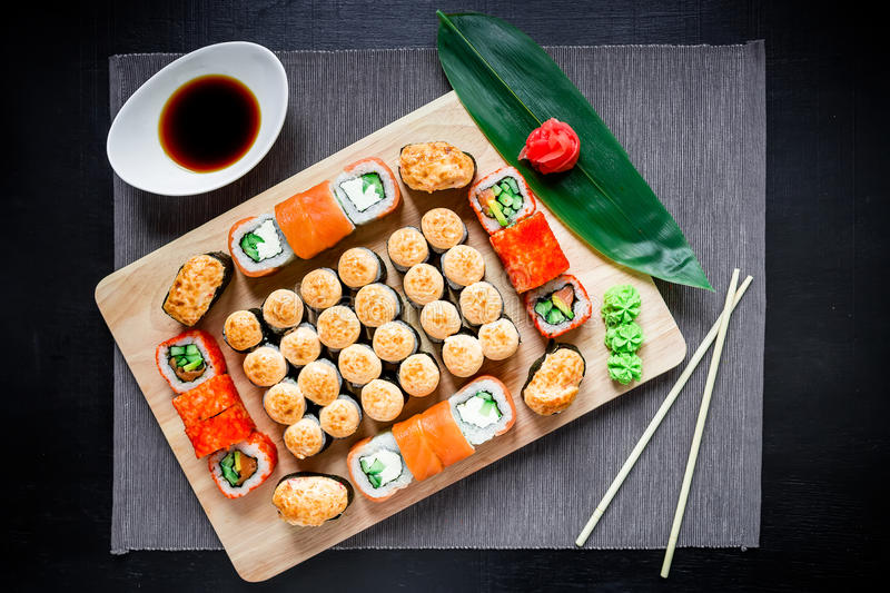 Japanese sushi rolls, soy sauce, ginger and chopsticks on a dark table. Top view. Flat lay. Japanese traditional food royalty free stock photography