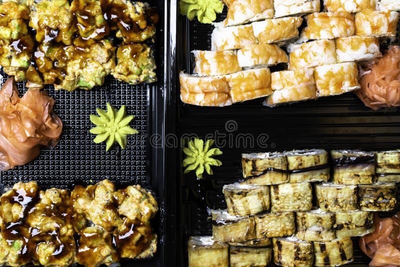 Japanese sushi set on black background. Sushi rolls, pickled ginger, wasabi Top view. Sushi background. Asian or Japanese food. Japanese sushi set on black stock photography