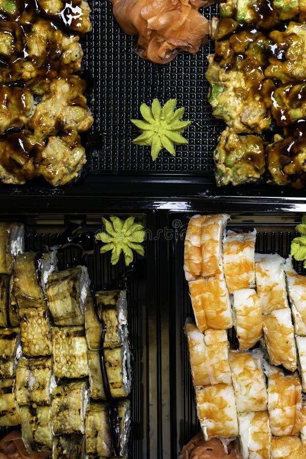 Japanese sushi set on black background. Sushi rolls, pickled ginger, wasabi Top view. Sushi background. Asian or Japanese food. Japanese sushi set on black royalty free stock images