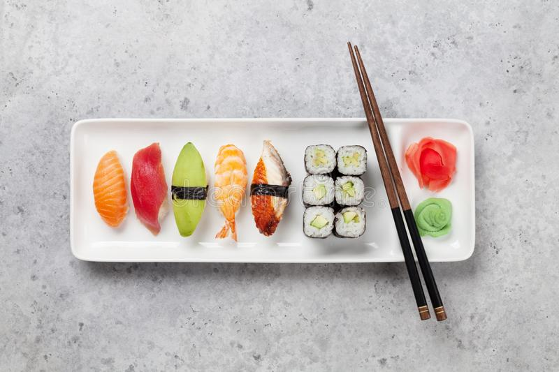 Japanese sushi set. Sashimi, maki rolls. On plate over stone background. Top view flat lay royalty free stock images