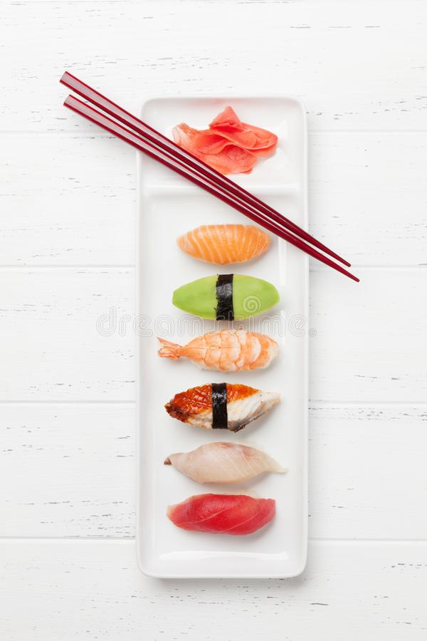 Japanese sushi set. Sashimi, maki rolls. On plate over wooden background. Top view flat lay stock photo