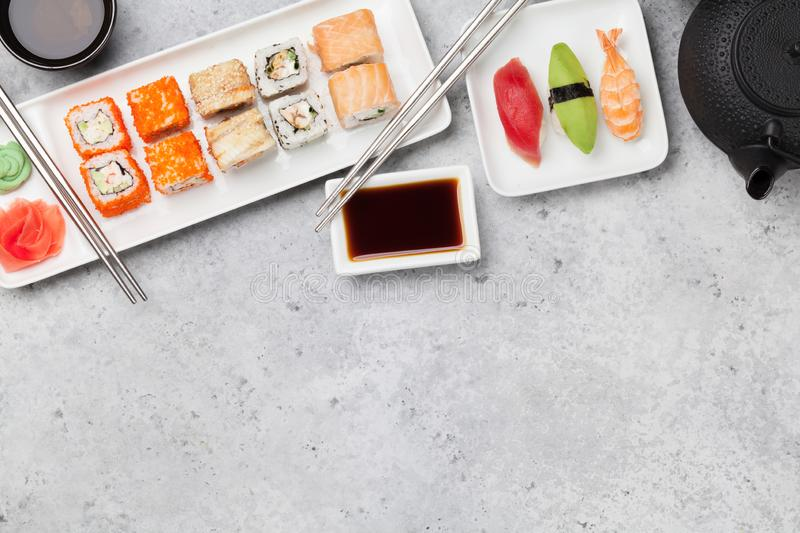 Japanese sushi set. Sashimi, maki rolls and green tea. On plate over stone background with space for your text. Top view flat lay stock images