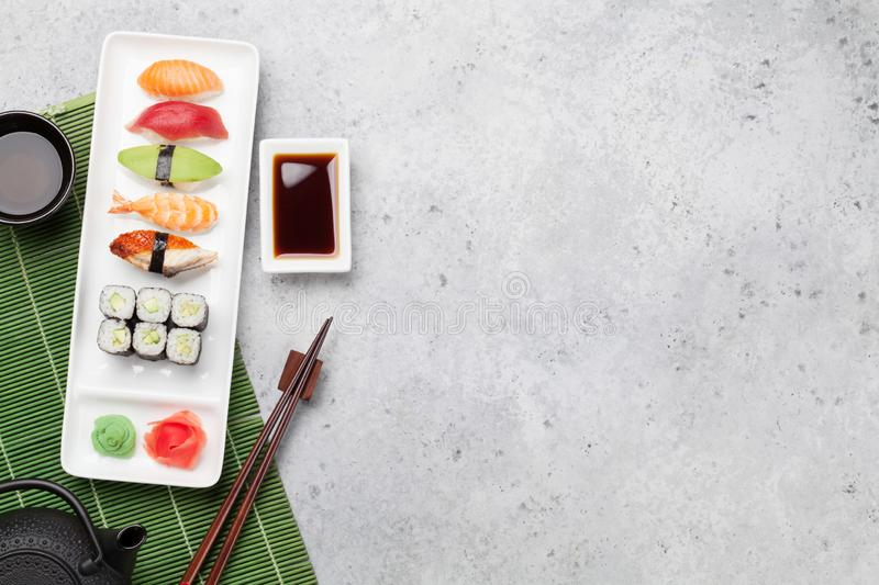 Japanese sushi set. Sashimi, maki rolls and green tea. On plate over stone background with space for your text. Top view flat lay stock photography