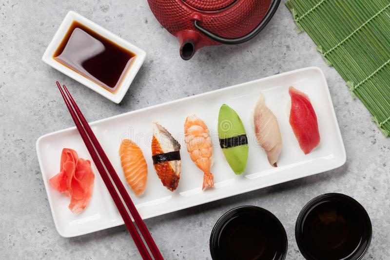 Japanese sushi set. Sashimi, maki rolls and green tea. On plate over stone background. Top view flat lay stock photos