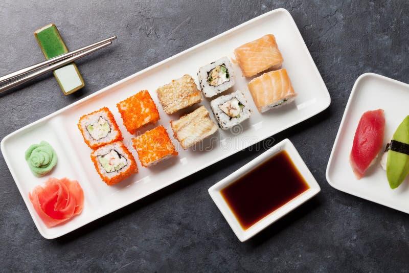 Japanese sushi set. Sashimi, maki rolls. On plate over stone background. Top view flat lay stock image