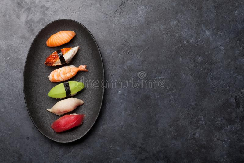 Japanese sushi set. Sashimi, maki rolls. On plate over stone background. Top view flat lay with copy space for your text royalty free stock images