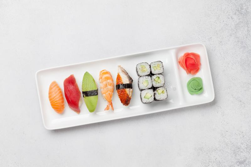 Japanese sushi set. Sashimi, maki rolls. On plate over stone background. Top view flat lay with copy space for your text stock photos