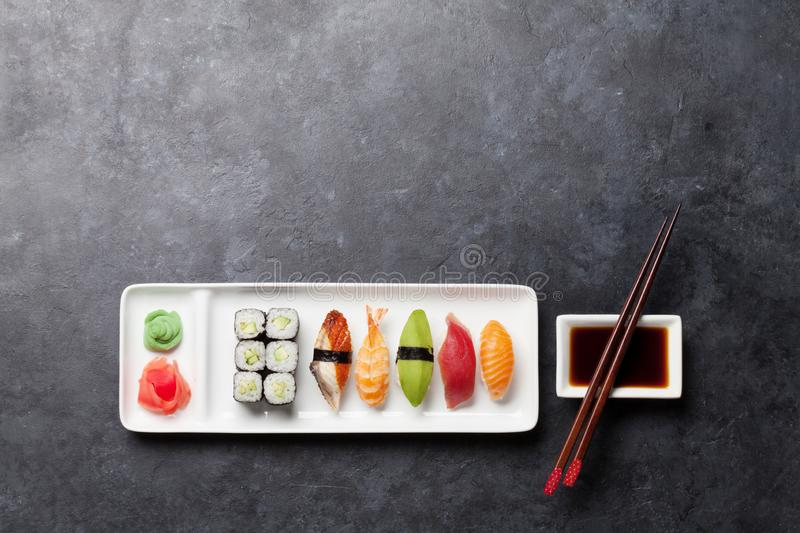 Japanese sushi set. Sashimi, maki rolls. On plate over stone background. Top view flat lay with copy space for your text stock photography
