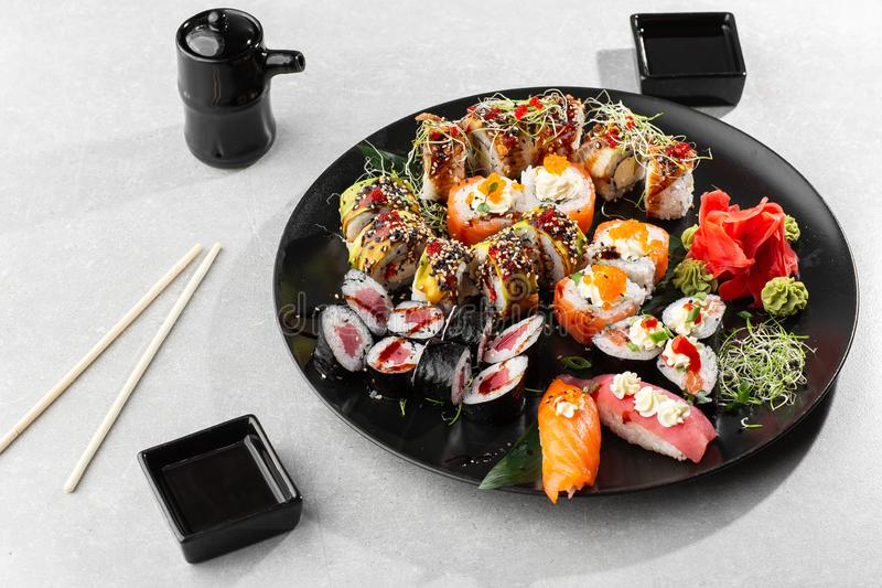 Japanese sushi set. Set of fresh tuna maki , salmon nigiri and dragon sushi rolls served on black plate close-up. Horizontal top. Japanese sushi set. Set of royalty free stock photos