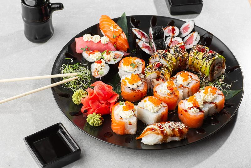 Japanese sushi set. Set of fresh tuna maki , salmon nigiri and dragon sushi rolls served on black plate close-up. Horizontal top. Japanese sushi set. Set of stock photo
